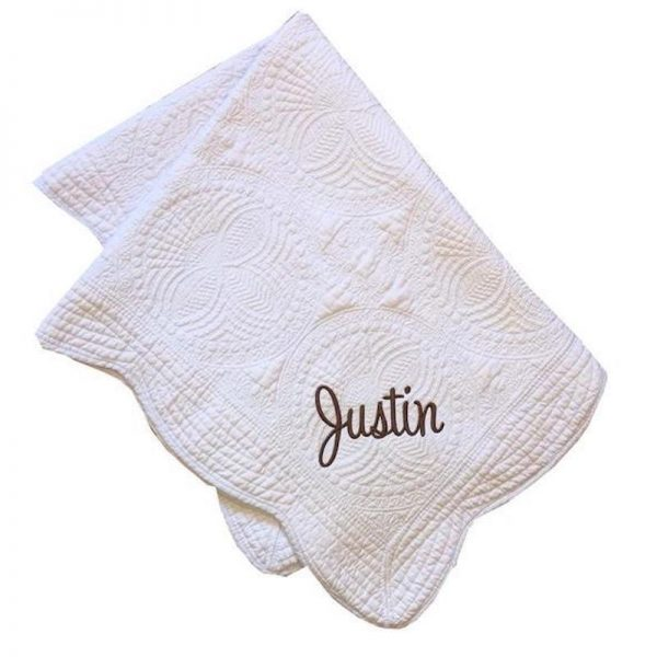 "white quilt with 'Justin"" embroidered on it"