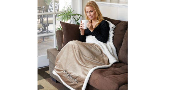 Woman sitting on couch with Personalized Tan Blanket